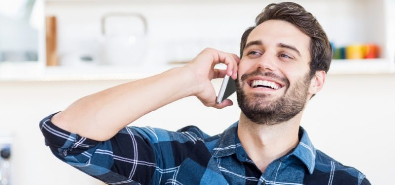 man on mobile device laughing